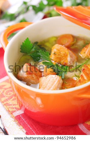 Soup with salmon and spring vegetables close-up - stock photo