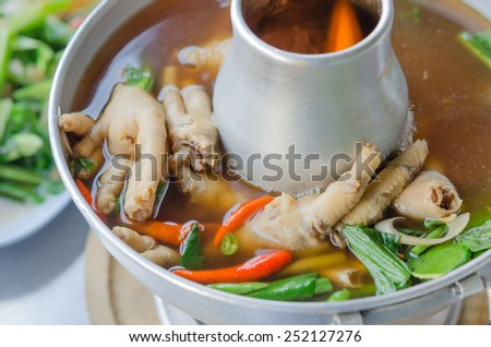 sour and spicy chicken feet soup in hot bowl - stock photo