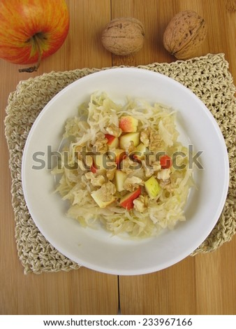 Sour cabbage salad with apples and walnuts - stock photo