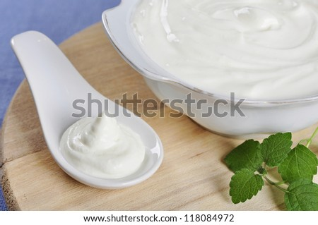 Sour cream in spoon on wooden cutting board. Small shallow DOF. - stock photo