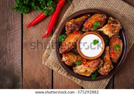 Sour-sweet baked chicken wings and sauce. Top view