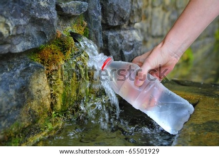 source of spring water bottle filling holding hand in Pyrenees mountain - stock photo