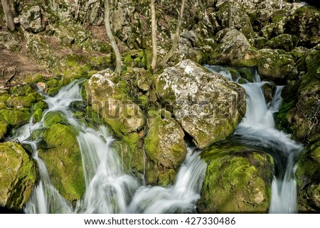 Source of the river that makes waterfalls over rocks covered with moss in early spring - stock photo