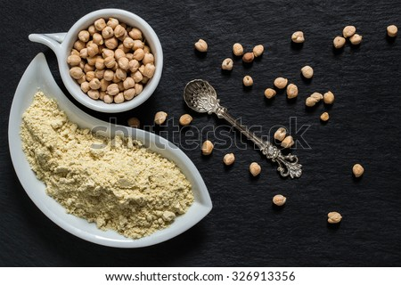 Source of vitamins A, E, groups B, manganese, calcium, selenium - chickpeas and chickpea gluten-free flour on a slate surface  - stock photo