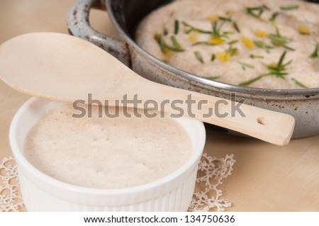 Sourdough in a white bowl on a antique cream doily and focaccia bread with rosemary in a oven pan - stock photo