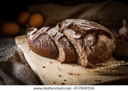 Sourdough rye bread sliced on wooden cutting board. Rustic still life. Natural light, low key