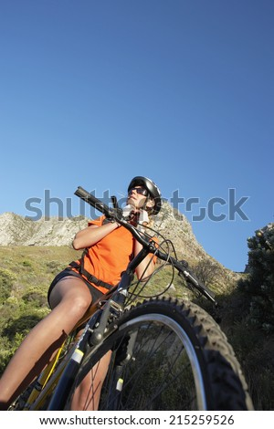 South Africa, female mountain biker adjusting cycling helmet strap, low angle view (tilt) - stock photo
