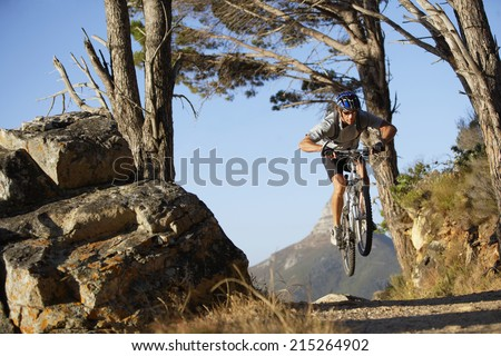 South Africa, male mountain biker in mid-air over dirt track, front view - stock photo
