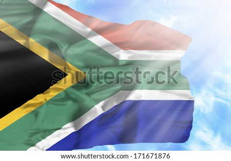 South Africa waving flag against blue sky with sunrays - stock photo