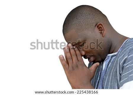 South African black young man with closed eyes and praying hands in his face. Image isolated on white studio background. - stock photo
