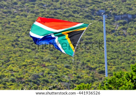 South African Flag fluttering in the wind along the coast of Cape Town, South Africa. - stock photo