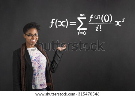 South African or African American black woman teacher or student holding her hand out to the side with a mathematical equation standing against a chalk blackboard background inside