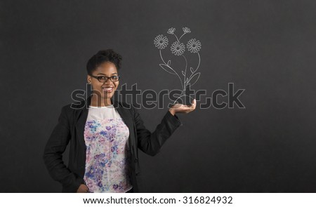 South African or African American black woman teacher or student holding her hand out to the side with a growing flower standing against a chalk blackboard background inside