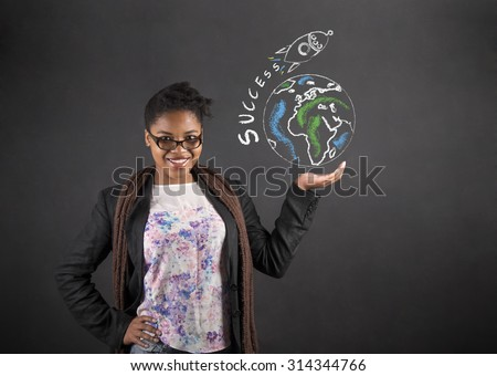 South African or African American black woman teacher or student holding the world success rocket in her hand standing against a chalk blackboard background inside - stock photo
