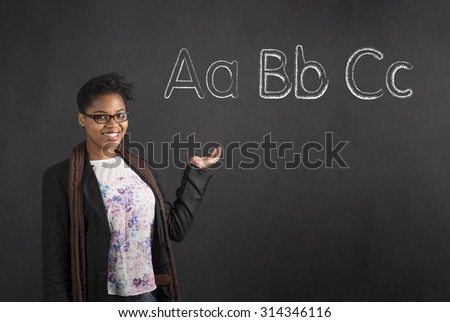 South African or African American black woman teacher or student showing or displaying the ABC alphabet standing against a chalk blackboard background inside