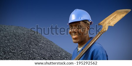South African or African American coal miner with coal pile - stock photo
