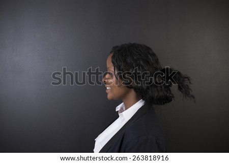 South African or African American woman teacher on chalk black board background - stock photo