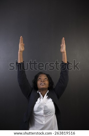 South African or African American woman teacher or student reaching for the sky on black background - stock photo