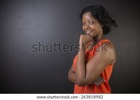 South African or African American woman teacher or student think or thinking on chalk black board background - stock photo