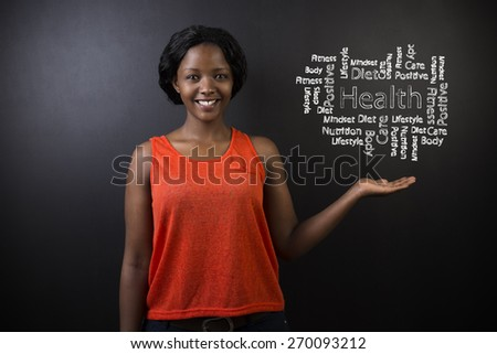 South African or African American woman teacher or student with her hand out standing against a blackboard background with a chalk health diagram - stock photo