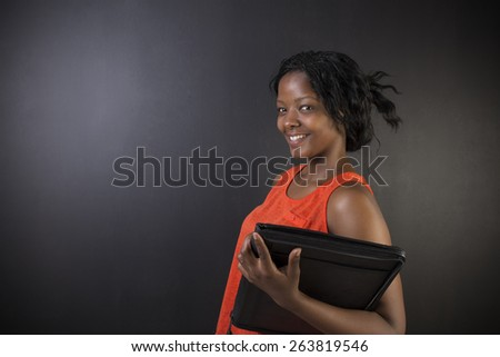 South African or African American woman teacher or student with notepad against a blackboard background - stock photo