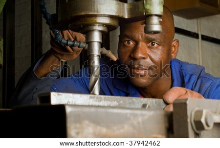 South African or American worker engineer working with industrial drill press - stock photo