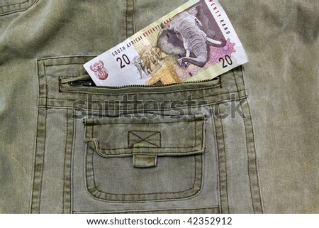 South African R20 note in the pocket of a pair of khaki trousers - stock photo