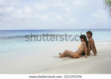 South American couple sitting on beach - stock photo