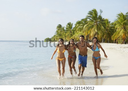 South American friends running at beach - stock photo