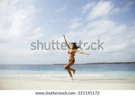 South American woman running on beach - stock photo