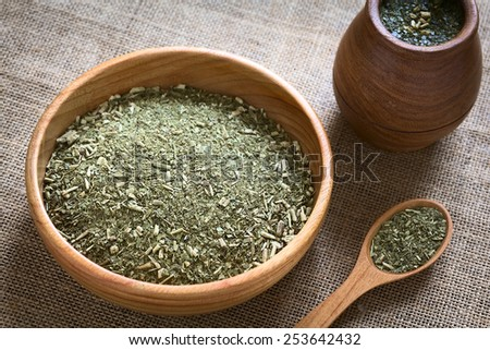 South American yerba mate (mate tea) dried leaves in wooden bowl with a wooden mate cup filled with tea photographed with natural light (Selective Focus, Focus in the middle of the dried tea leaves)  - stock photo