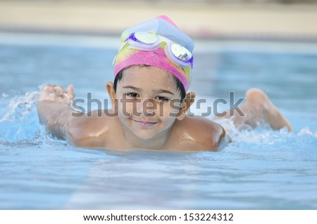 South Asian Indian Arab kid having a good time in arab  swimming pool - stock photo