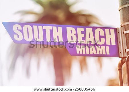 South Beach Miami Street Sign. A street sign marking South Beach, Miami. Backed by a palm tree with a sunset flare. - stock photo