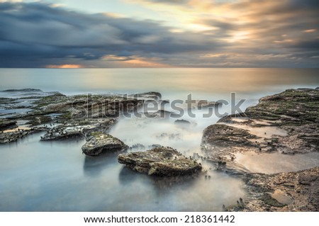 South Curl Curl looking very serene in this long exposure of the ocean and rocks at sunrise - stock photo