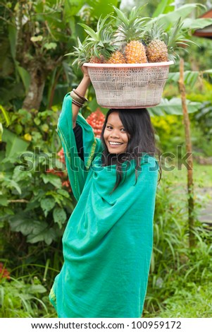 South-east asian woman carrying a basket of pineapples on her head - stock photo