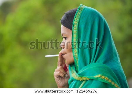 South-east asian woman with head dress smoking - stock photo