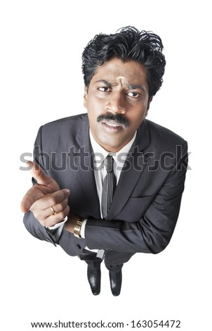 South Indian businessman gesturing and looking serious - stock photo