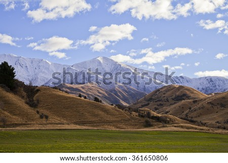 South Island mountain landscape scenery with a grass field in the foreground, Central Otago, New Zealand - stock photo