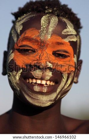 SOUTH OMO - ETHIOPIA - JANUARY 9: Unidentified young Suri man with face painting on January 9, 2012 in South Omo, Ethiopia. A 5-year resettlement programm started 2011 threatens tribes in Ethiopia.