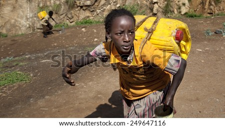 SOUTH OMO - ETHIOPIA - NOVEMBER 19, 2011: Unidentified girl bears the canister with water, in November 19, 2011 in Omo Rift Valley, Ethiopia. - stock photo