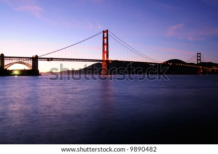 South tower of Golden Gate Bridge glows against beautiful sunset sky with Fort Point lit by fluorescent floodlight. - stock photo