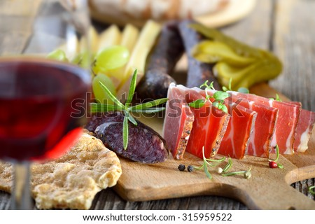 South Tyrolean hearty snack with bacon (speck), spicy mountain cheese, cured sausages and bread, served with a glass of red wine - stock photo