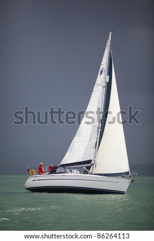SOUTHAMPTON, UK - SEPT. 18: An unidentified boat sails near Southampton with dark sky in the background on September 18, 2011 in Southampton, U.K. Southampton is one of UK's most famous sailing spot. - stock photo