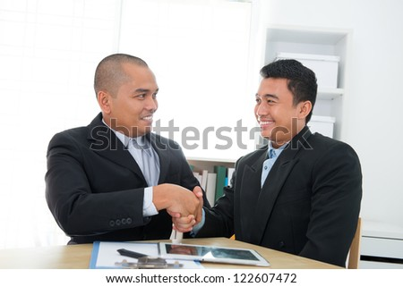 Southeast Asian business deal in office - stock photo