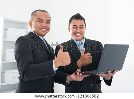 Southeast Asian business people thumbs up, holding notebook in workplace