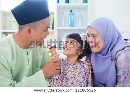 Southeast Asian girl feeding ice cream to father. Malay Muslim family lifestyle - stock photo