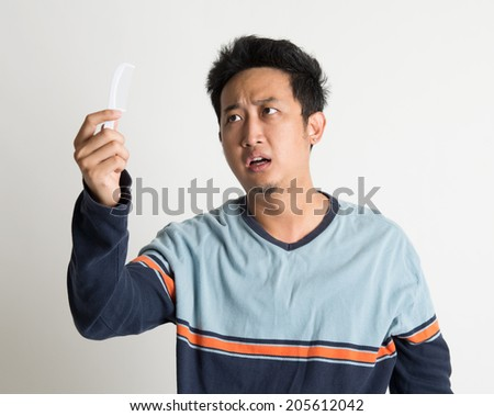 Southeast Asian man checking on a comb with shock facial expression, on plain background. - stock photo