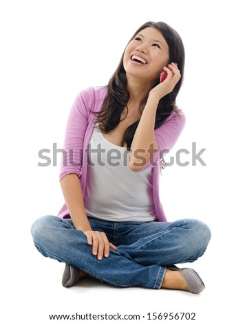 Southeast Asian woman talking on smartphone, full body sitting over white background - stock photo