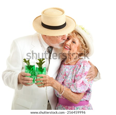 Southern senior couple dressed for the Kentucky Derby,  holding mint juleps and kissing.