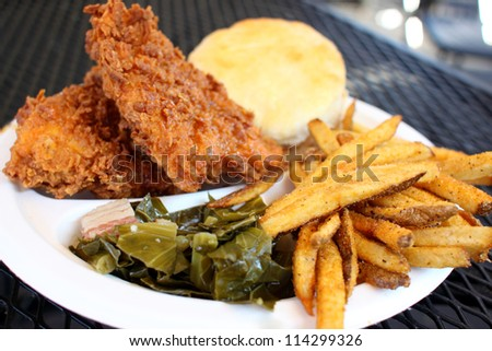 Southern style meal with fried chicken, collard greens with bacon, French fries, and a biscuit. - stock photo